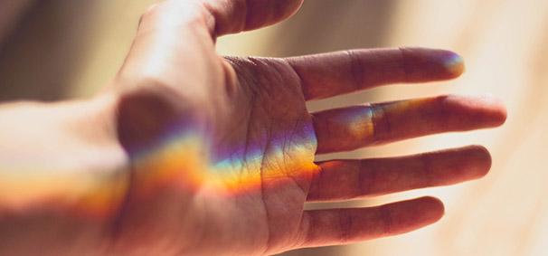 Hand mit buntem Lichtmuster