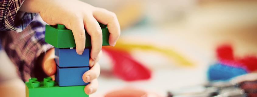 Kinderhände und Spielzeug